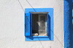 Blue and white shuttered window in wall on Greek Island. White and blue wall with blue shuttered window on Island of Psirimos in Greece royalty free stock photos