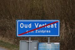 Blue and white sign with red line to mark the end of the urban area in Oud Verlaat in the Netherlands. Blue and white sign with red line to mark the end of the stock images