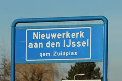 Blue and white sign to mark the start of the urban area in Nieuwerkerk aan den IJssel in the Netherlands. Blue and white sign to mark the start of the urban stock photography