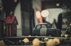 Blue and white small car toy model on the road. Mini car toy in the city near building on blurred background with bokeh. Cartoon. Miniature car. World of royalty free stock images