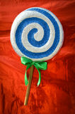 Blue and white spiral lollipop on red background Stock Photo