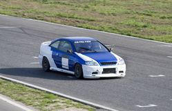 Blue-white sportcar. In a circuit race Royalty Free Stock Photography