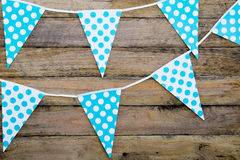 Blue and white spotted bunting flags hanging against rustic timb Royalty Free Stock Image