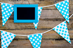 Blue and white spotted bunting flags hanging against rustic timb Stock Photos