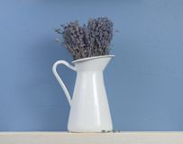 Blue and white still-life with lavender. Bunch of lavender in white enamelled milk jug standing on the shelf on the blue stucco wall background Stock Image