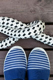 Blue and white striped sailor style shoes and rope with a knot on a brown wooden dock. Vertical image Stock Photos