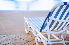 Blue and white striped sunbed near swimming pool in holiday resort. Royalty Free Stock Photography