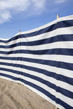 Blue and white striped windbreak at the beach Royalty Free Stock Image