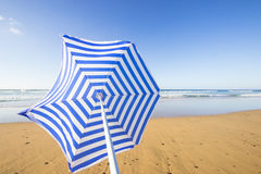 Blue and white sunshade flying away Royalty Free Stock Photos