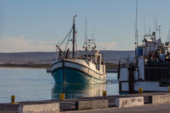 Blue and white trawler approaching dock Stock Image