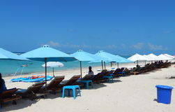 Blue and white umbrellas and chaise longue. White and blue umbrellas and chaise longue on Pandawa beach Bali stock photo