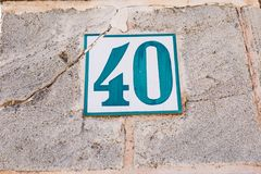 Blue white vintage house number forty 40 on a old aged wall.  stock images