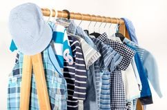 Dressing closet with baby boy clothes arranged on hangers. stock photography