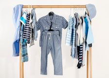 Dressing closet with baby boy clothes arranged on hangers. royalty free stock photography