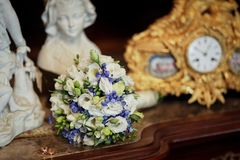 Blue and white wedding bouquet laying on the table in the vintage interior stock photo