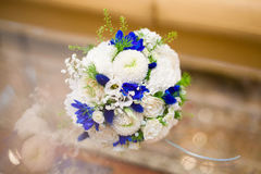 Blue and white wedding bouquet of roses on glass table. Beautiful blue and white wedding bouquet of roses on glass table Stock Image