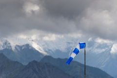 Blue-white windsock. At the summit of the Nebelhorn before massif with dark clouds Royalty Free Stock Photo