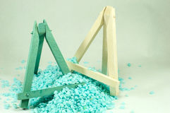 Blue and white wooden mini easels, which are bombarded by small blue stones. Royalty Free Stock Photos