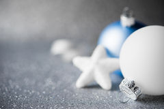 Blue and white xmas ornaments on glitter holiday background. Merry christmas card. Stock Image