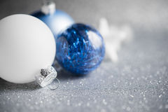 Blue and white xmas ornaments on glitter holiday background. Merry christmas card. Stock Photo