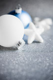 Blue and white xmas ornaments on glitter holiday background. Merry christmas card. Stock Photos