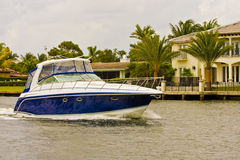 Blue and White Yacht Past Mansions royalty free stock images