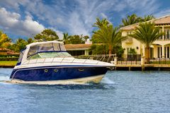 Blue and White Yacht Past Mansions royalty free stock photos