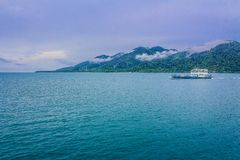 Blue and White Yacht on Teal Sea Near Green Mountain Stock Photo