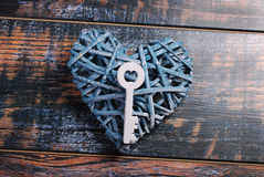 Blue wicker heart and a key on shabby wooden background Stock Photo