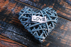 Blue wicker heart on shabby wooden background Royalty Free Stock Photography