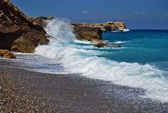 Blue wild water runs along the rocks on the beach under blue sky in Crete Stock Photos