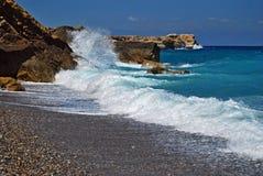 Blue wild water runs along the rocks on the beach under blue sky in Crete Stock Photos