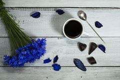 Blue wildflowers with a cup of coffee and candies. On a white wooden table stock photo
