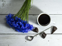 Blue wildflowers with a cup of coffee and candies. On a white wooden table royalty free stock image