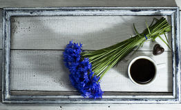 Blue wildflowers with cup of coffee in the old frame. Blue wildflowers with a cup of coffee and candies in the old frame on a white wooden background stock photos