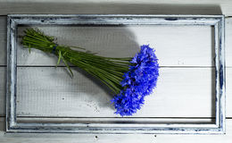 Blue wildflowers in the old frame. On a white wooden background royalty free stock photos