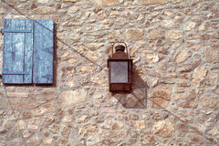 Blue window. Old lamp and a wall of a rural house stock image
