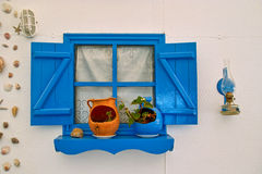 Blue window. Beautifully decorated window decorated with shells and lamps, painted in blue on a house by the sea. Picture taken 141.09.2010 Royalty Free Stock Photos
