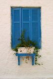 Blue window. Beautifully window decorated with flowerpot, painted in blue on a house by the sea. Picture taken 14.09.2010 Stock Image