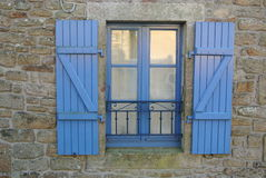 Blue window. Ancient window colored blue with the setting sun which is reflected in the glass Stock Images