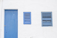 Blue window and door made out of wood and white wall. Royalty Free Stock Images