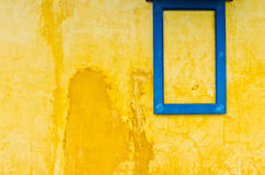 Blue window frame on yellow wall Stock Photo