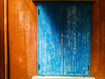 Blue window and orange wall with sun light and soft shadow Stock Image