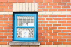 Blue window in red brick wall. Stock Photos