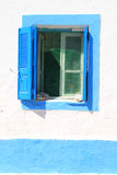 Blue window with shutters on Greek Island. Blue window with louvre shutters and mesh screen on Greek island royalty free stock photo
