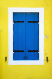 Blue window shutters on a yellow house wall Royalty Free Stock Image
