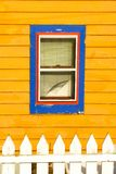 Blue window on yellow house royalty free stock photography