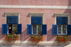 Blue windows with geraniums Stock Image