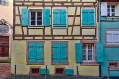 Blue windows on pale yellow walls of a small town. Blue windows on pale yellow walls of a traditional house in Colmar, Alsace, France Stock Photos
