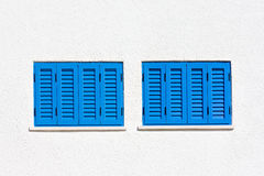 Blue windows on the white wall. Two blue windows on the white wall royalty free stock image